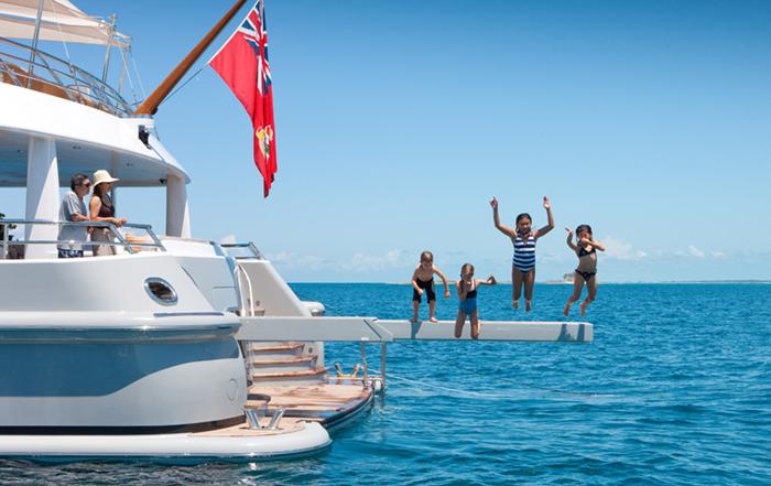 Children jumping off a yacht
